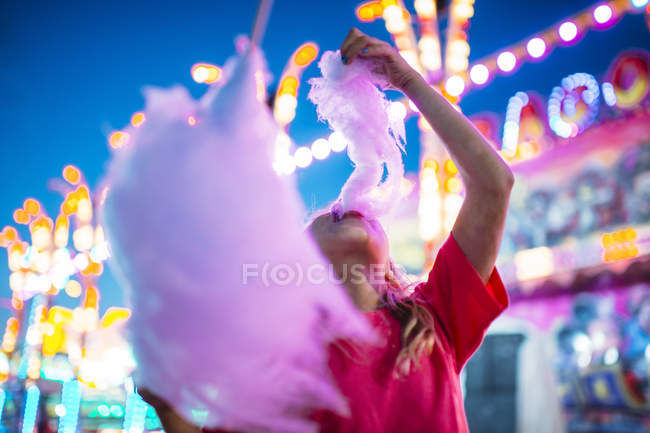 Little girl eating candyfloss in the summer amusement park — Stock Photo