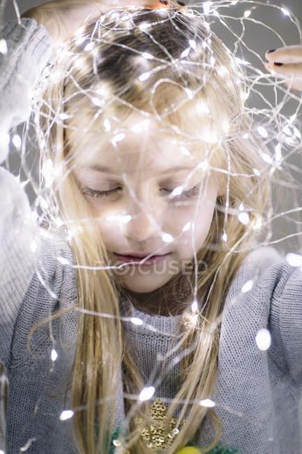 Bonito loira preteen menina com iluminado natal luzes na cabeça — Fotografia de Stock