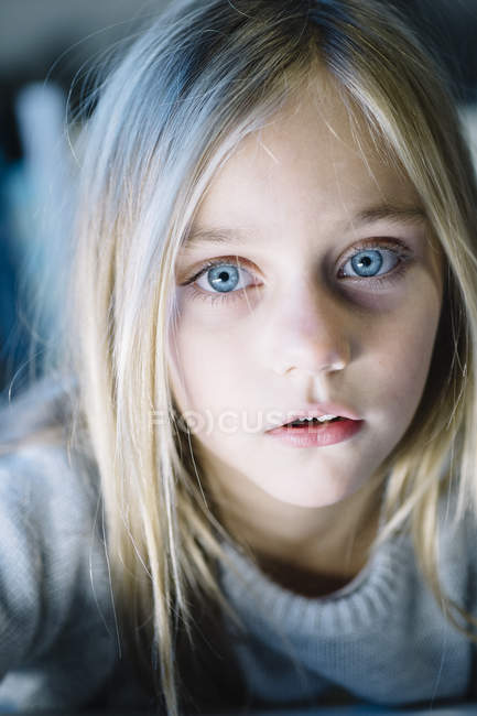 Beautiful blonde preteen girl with big blue eyes looking at camera — Stock Photo
