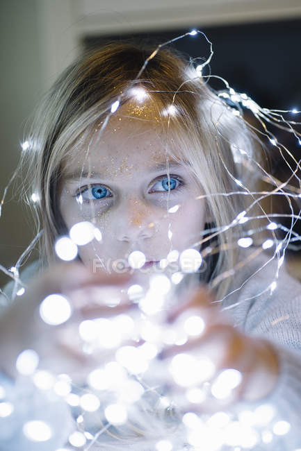 Adorable blonde girl with blue eyes wearing christmas lights — Stock Photo