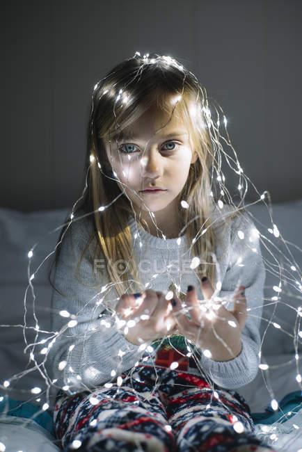 Bela loira preteen menina vestindo iluminado natal guirlanda com lâmpadas brilhantes — Fotografia de Stock