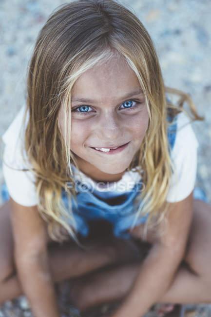 Красивая блондинка с голубыми глазами, сидящая на полу и смотрящая в камеру — стоковое фото