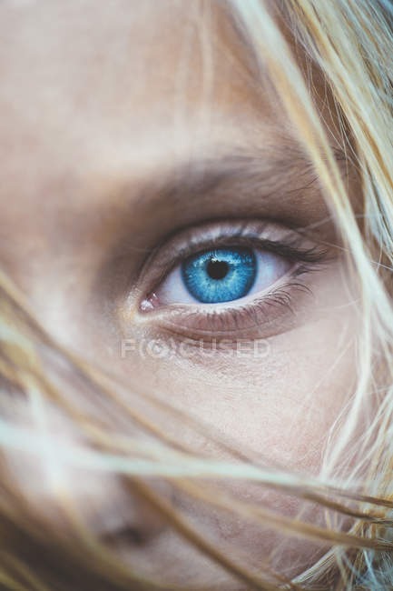 Close up shot of beautiful blonde preteen girl, partial view of blue eye — Stock Photo