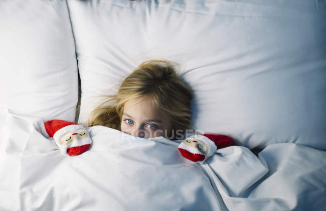 Cute little girl lying with under the blanket in bed and waiting for Santa Claus — Stock Photo