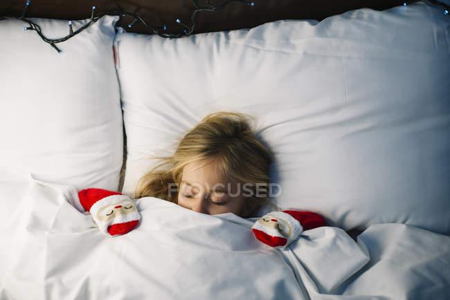 Loirinha deitada com os olhos fechados, na cama, debaixo do cobertor e esperando por Papai Noel — Fotografia de Stock