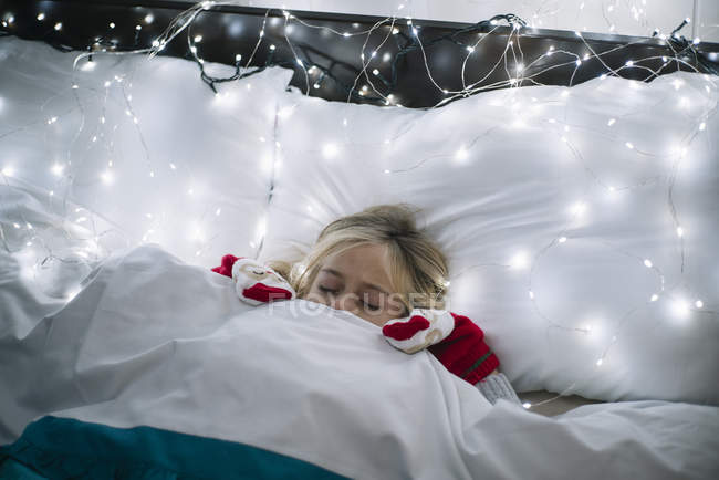 Little blonde girl lying in bed under the blanket, christmas garland with glowing light bulbs on pillows — Stock Photo