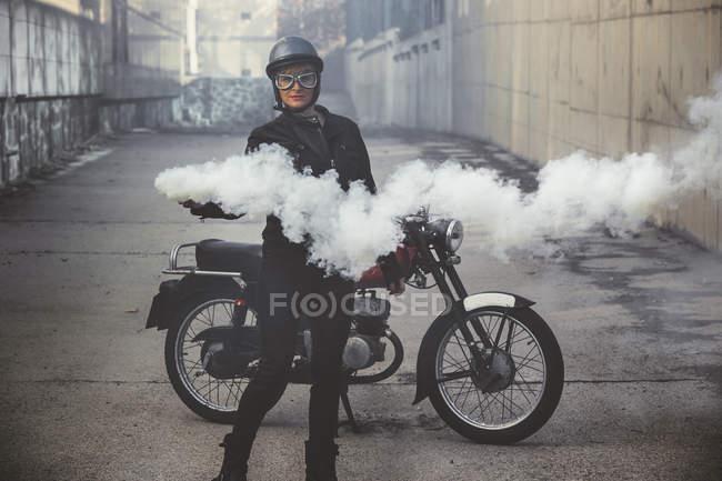 Femme moto dans la rue tenant une fusée éclairante de fumée — Photo de stock