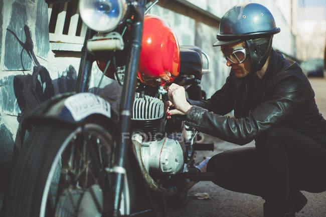 Motorbike woman arranges damaged motorcycle — Stock Photo