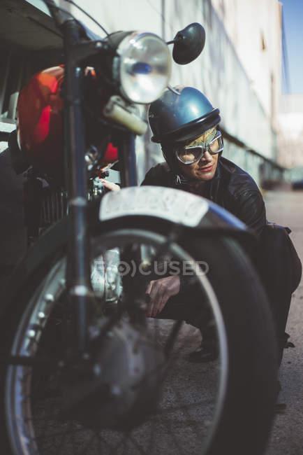 Motorradfahrerin sorgt für beschädigtes Motorrad — Stockfoto