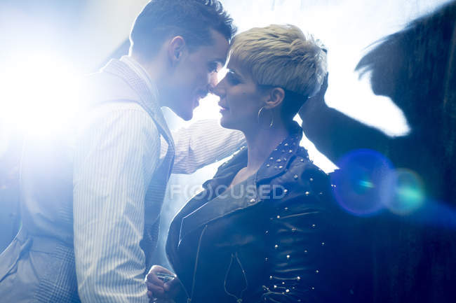 Hombre en el desgaste clásico y la mujer punk de pie cerca el uno del otro - foto de stock