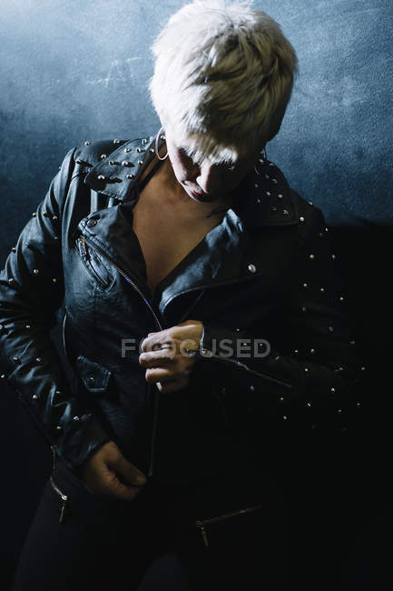 Portrait of short haired woman zipping leather jacket — Stock Photo
