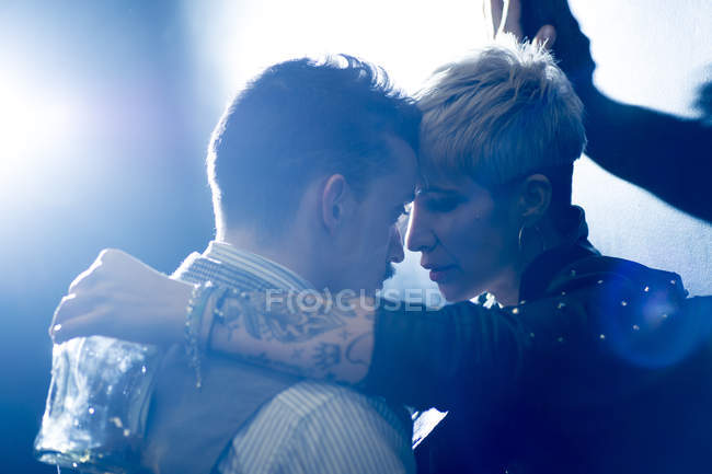 Man in classic wear and tattoed woman holding bottle, looking at each other close — Stock Photo