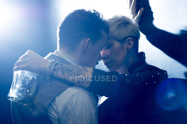 Man in classic wear and tattoed woman holding bottle, coming closer to kiss — Stock Photo