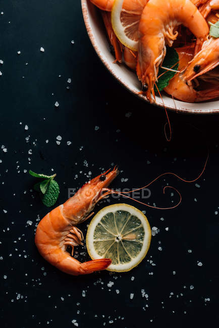Elevated view of lemon slices, mint leaves, shrimps and plate on table with salt — Stock Photo