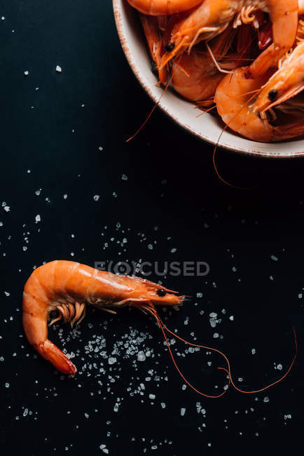 Top view of plate with shrimps on dark table with salt — Stock Photo