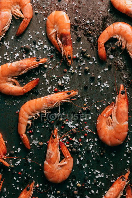 Top view of shrimps on table with black pepper and salt — Stock Photo
