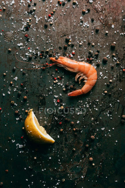 Top view of shrimp and lemon slice on surface with salt and black pepper — Stock Photo
