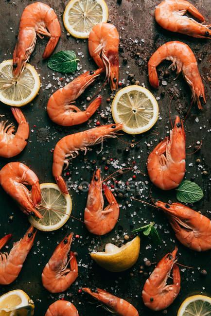 Vista elevata di fette di limone, menta foglie e gamberetti su tavolo con pepe nero e sale — Foto stock