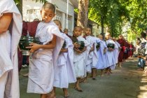 Daily procession of Buddhist novices monks walking for collection alms and offerings in Amarapura near Mandalay, Myanmar. — Stock Photo