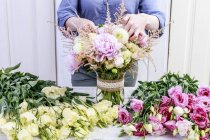 Female florist arranging bouquet with pink peonies, roses and yellow dahlias. — Stock Photo