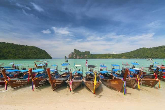 Туристичні прикрашені гірляндами довгий хвіст човни на пляжі, Пхі-Пхі, Таїланд — стокове фото