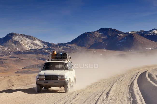 Carro de turista atravessando o planalto deserto de Atacama, na Bolívia, América do Sul — Fotografia de Stock