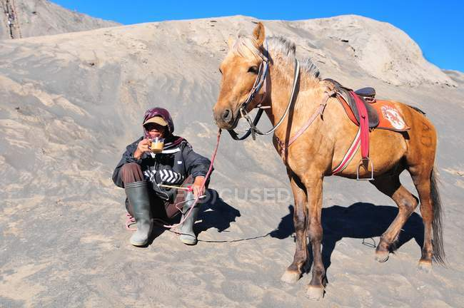 Indonesia man with horse for tourist rent at Mount Bromo of Tengger massif, in East Java. — Stock Photo