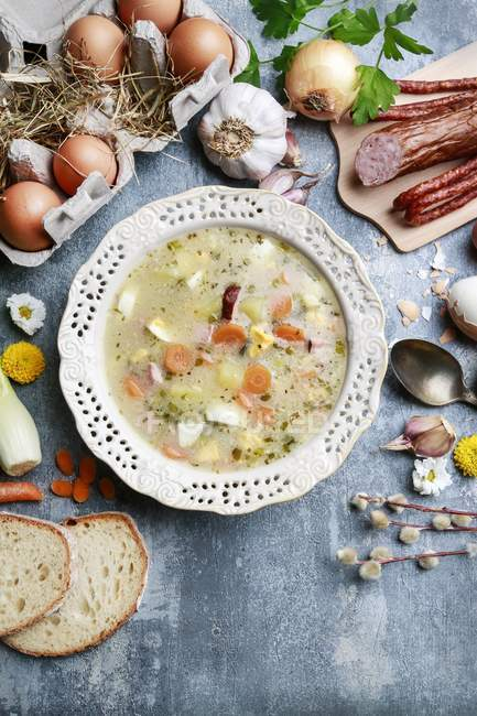 Traditional polish rye soup on table with meat, eggs and vegetables. — Stock Photo
