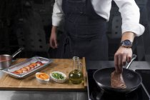 Cropped view of male chef roasting steak — Stock Photo