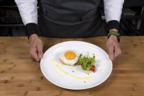 Cropped view of male chef holding plate with fried egg on toast — Stock Photo