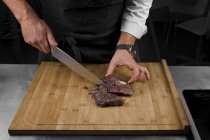 Cropped view of male chef cutting meat — Stock Photo