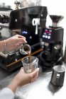 Close-up view of female barista hands pouring espresso — Stock Photo