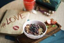 Миска овсянки с сухофруктов, орехов и ягод варенье на столе — стоковое фото