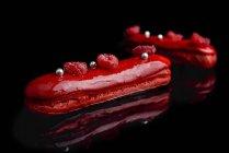 Eclairs com esmalte vermelho e framboesas frescas — Fotografia de Stock