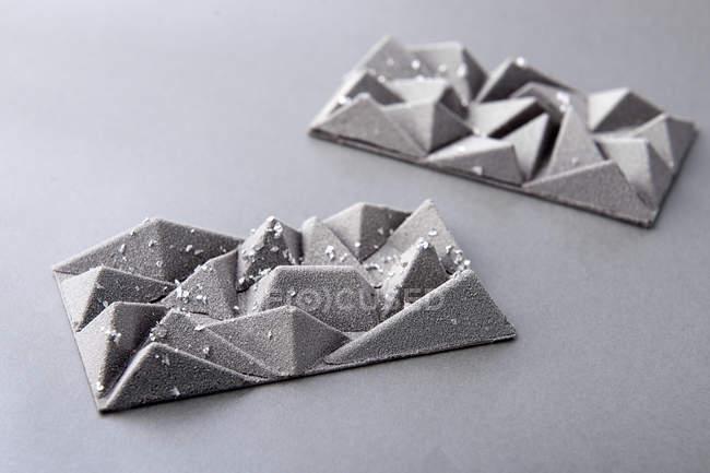 Barras de chocolate de postre plata con diseño geométrico sobre fondo gris - foto de stock