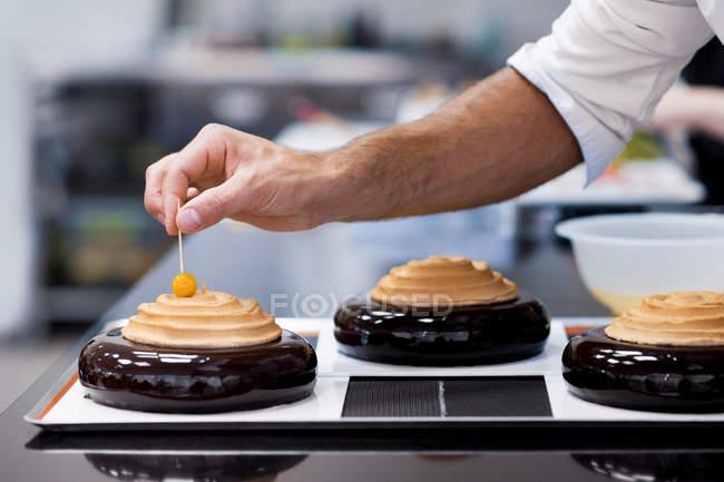 Primer plano de hombre chef decoración de pastel con cereza - foto de stock