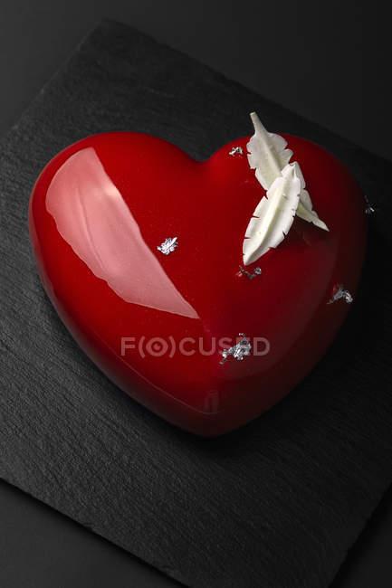 Pastel de cristal en forma de corazón con plumas chocolate - foto de stock