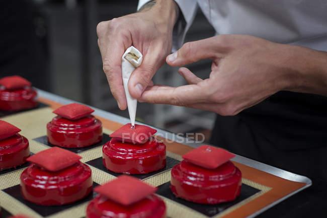 Primer plano del chef, decoración de tortas con dulces perlas - foto de stock