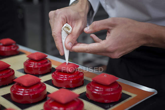 Close-up of chef decorating cakes with pearl candies — Stock Photo
