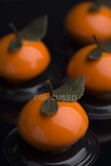 Fruit-shaped cakes with chocolate leaves — Stock Photo
