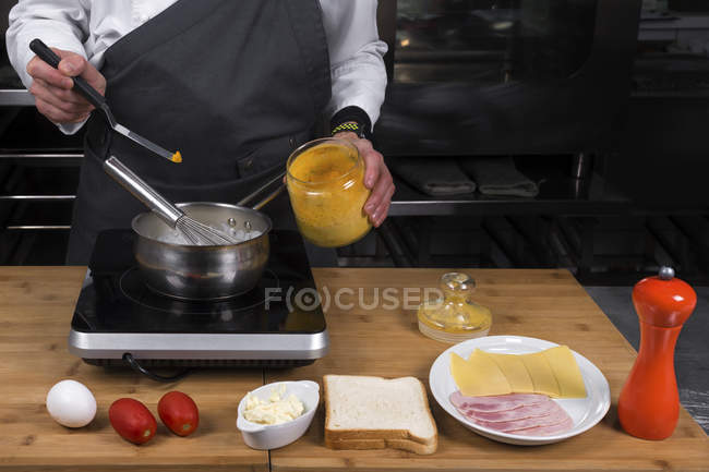 Cropped view of male chef making curry sauce — Stock Photo