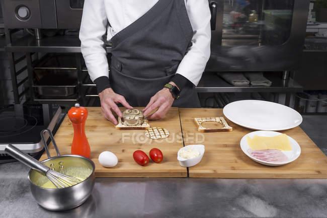 Ansicht der männlichen Chef schneiden Toast mit Form beschnitten — Stockfoto