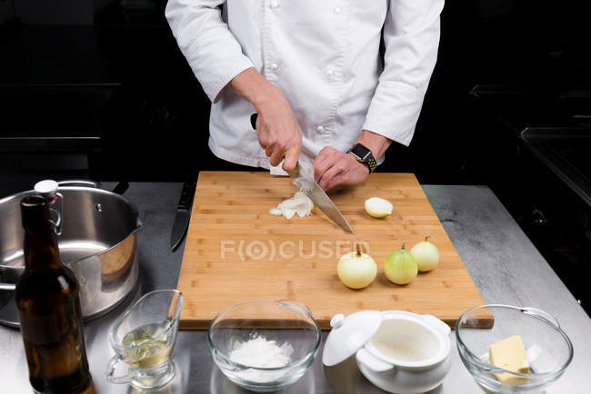 Cropped view of male chef cutting onions — Stock Photo
