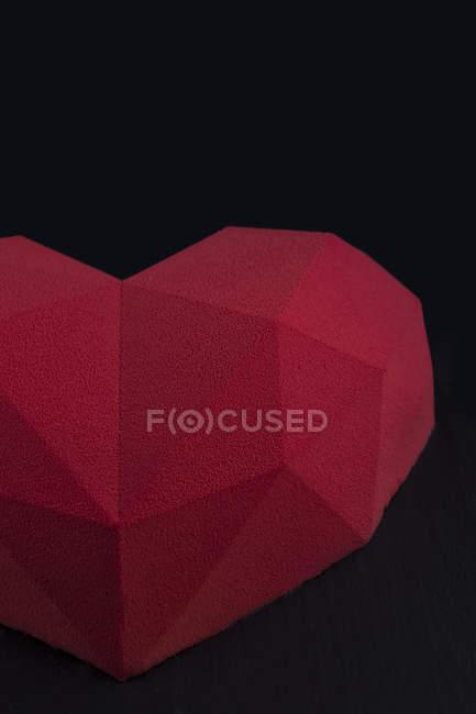 Torta rossa a forma di cuore su sfondo nero — Foto stock