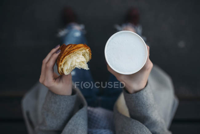Woman holding croissant and cup of cappuccino — Stock Photo