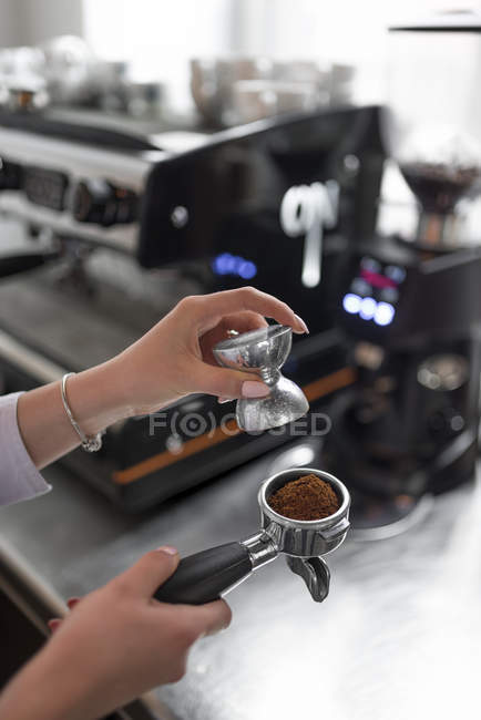 Close-up view of female barista hands filling coffee machine — Stock Photo