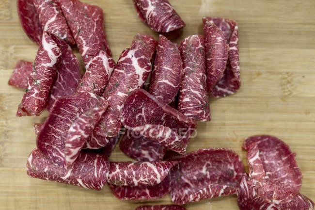 Нарезанный fuet колбаса с травами на деревянной доске — стоковое фото