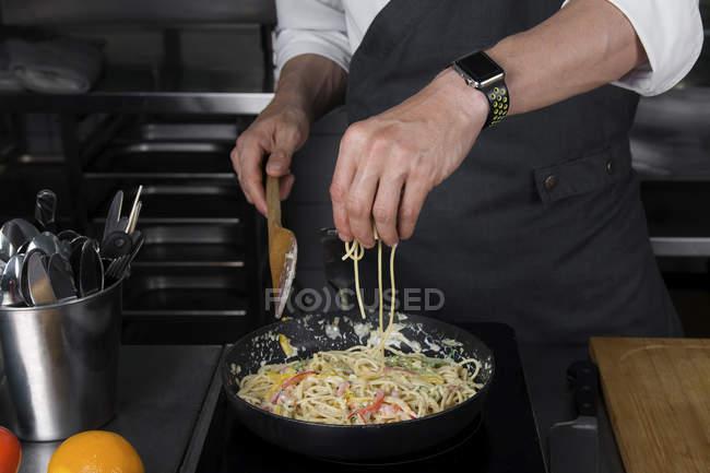 Vista recortada de chef masculino cocinando pasta - foto de stock