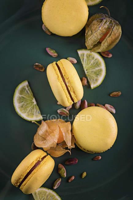 Macarons giallo con frutti di physalis e fette di limone — Foto stock