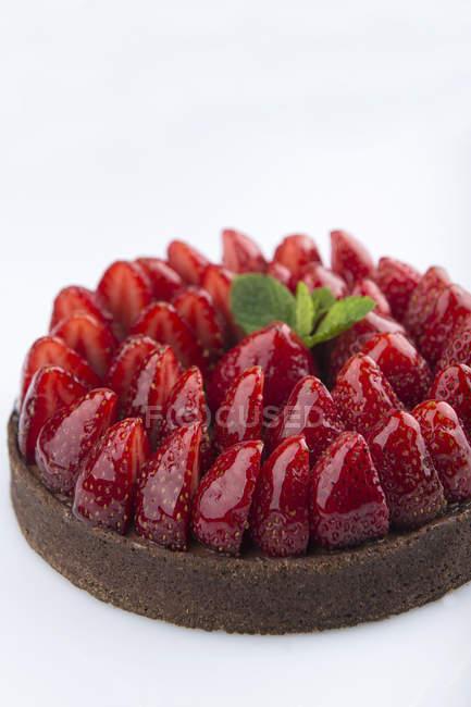 Bolo de chocolate com morangos frescos em fundo branco — Fotografia de Stock